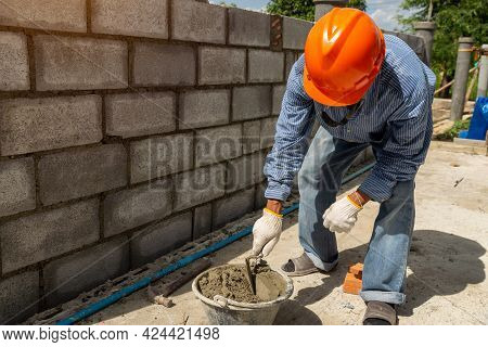 Masonry Worker Make Concrete Wall By Cement Block And Plaster At Construction Site.