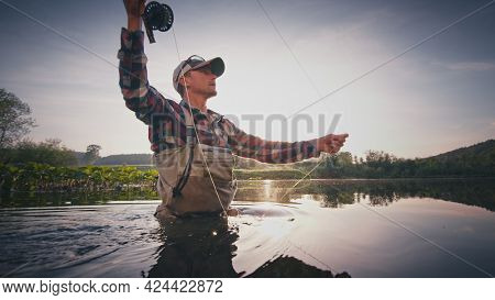 Fly fisherman stands in the water and casts the fly with fishing rod