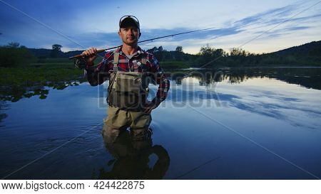Fly fisherman stands on the river and looks into the camera