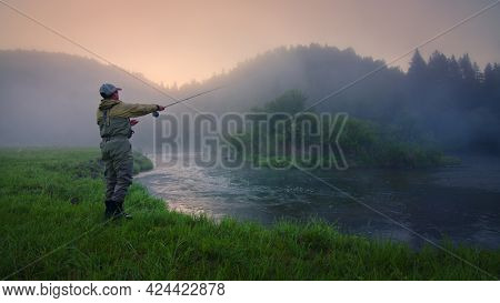 Fly fisherman fishing on the river at foggy sunrise