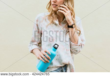 Woman on the phone carrying a thermal bottle