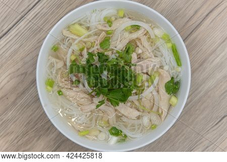 Overhead View Of Hearty Bowl Of Chicken Pho Loaded With Meat, Broth, And Topped With A Sprig Of Cila
