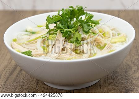 Hearty Bowl Of Pho Loaded With Meat, Broth, And Topped With A Sprig Of Cilantro For A Complete Meal.