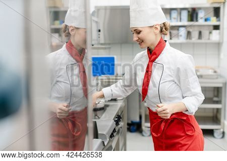 Cook in large commercial kitchen stirring sauce
