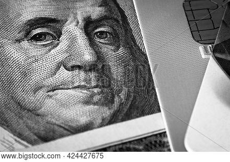 Benjamin Franklin's Face On A Hundred-dollar Bill Next To A Credit Card. Close-up. A Hundred-dollar