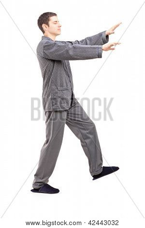 Full length portrait of a young man in pajamas sleepwalking isolated on white background