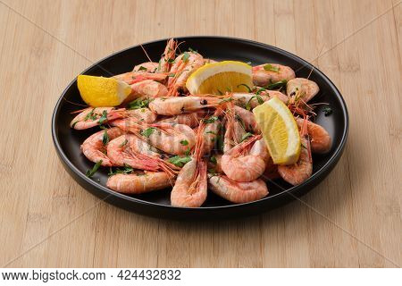 Boiled Shrimp Garnished With Lemon And Parsley In A Dark Plate On A Light Wooden Background.