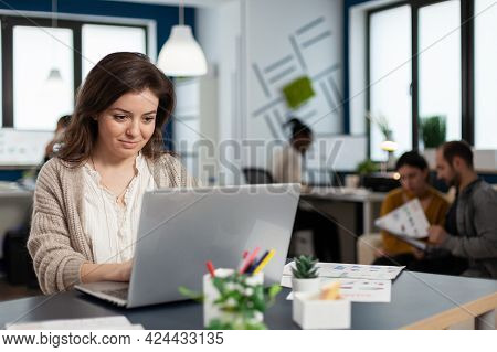 Close Up Of Satisfied Businesswoman Answering Email Typing On Laptop Smiling Sitting At Desk In Busy