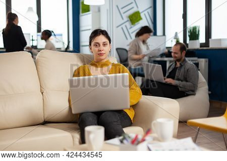 Young Woman Entrepreneur Sitting On Couch In Middle Of Business Start Up Office Looking At Camera Sm