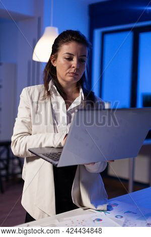 Tired Entrepreneur Analysing Financial Reports Standing In Start Up Office Holding Professional Lapt