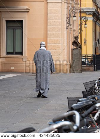 Parma, Italy - June 2021: African Man With A Long Gray Tunic And A Hat Walking Near The Central Stat