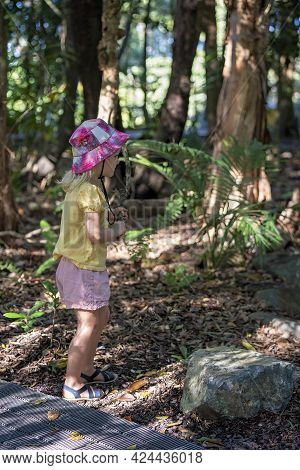Mackay, Queensland, Australia - June 2021: Three Year Old Girl With Stick In Hand Investigating What