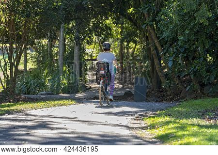 Mackay, Queensland, Australia - June 2021: A Mother Cycles On A Bike In The Botanic Gardens With Her