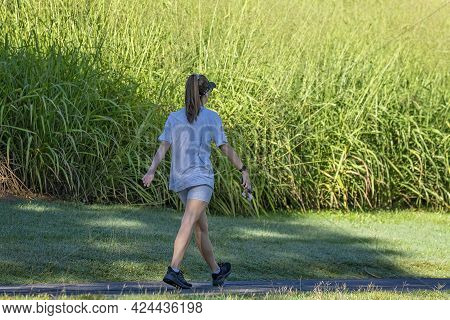 Mackay, Queensland, Australia - June 2021: A Young Woman Strides Out As She Walks For Exercise In Th