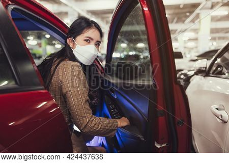 Asian Woman Using A Surgical Mask Open A Car Door While Looking At The Camera At Car-park Background