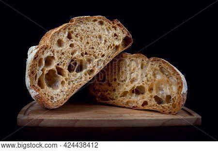 A Loaf Of Rye Bread Cut In Half On A Wooden Cutting Board. Homebaked Bread .