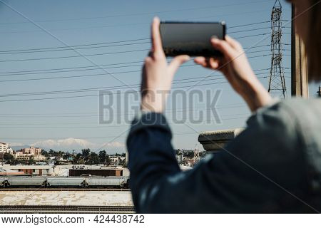 Woman capturing a view at a platform by her phone