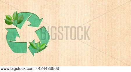Arrows recycle symbol and green leaves on cardboard texture. Horizontal banner with eco paper texture. Paper cardboard background. Recycled carton material. Copy space for text. Mock up template