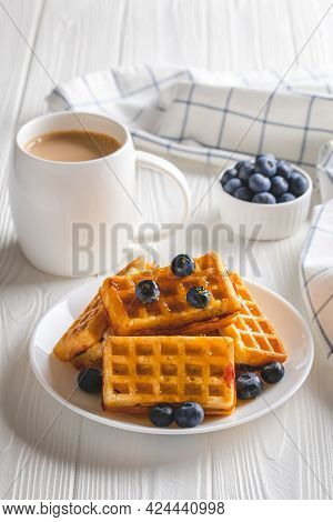 Belgian Waffles With Berries And Coffee On A White Wooden Table. Hot Morning Drink And Blueberries,