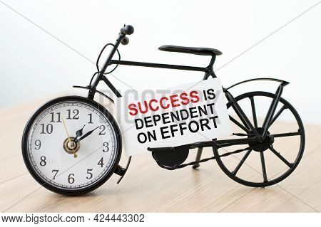 Text Success Is Dependent On The Effort Of The Card Next To The Watch On A Light Background