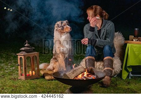 Young Woman Is Eating A Slice Of Baguette With Brie. Her Young Australian Shepherd Dog Sits Next To