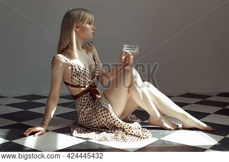 Woman With Glass Alcohol In Hand Sit On Floor, An Old Interior, Romantic Look Blonde Girl. Shadow Of