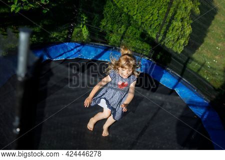 Little Preschool Girl Jumping On Trampoline. Happy Funny Toddler Child Having Fun With Outdoor Activ