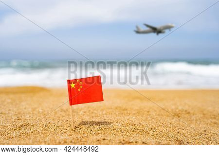 Flag Of China In The Form Of A Toothpick In The Sand Of Beach Opposite Sea Wave With Landing Airplan