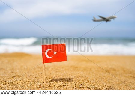 Flag Of Turkey In The Form Of A Toothpick In The Sand Of Beach Opposite Sea Wave With Landing Airpla