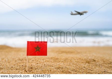 Flag Of Morocco In The Form Of A Toothpick In The Sand Of Beach Opposite Sea Wave With Landing Airpl