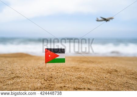 Flag Of Jordan In The Form Of A Toothpick In The Sand Of Beach Opposite Sea Wave With Landing Airpla