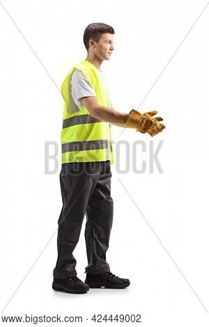 Full length profile shot of a young waste collector in a uniform and gloves gesturing with hands isolated on white background