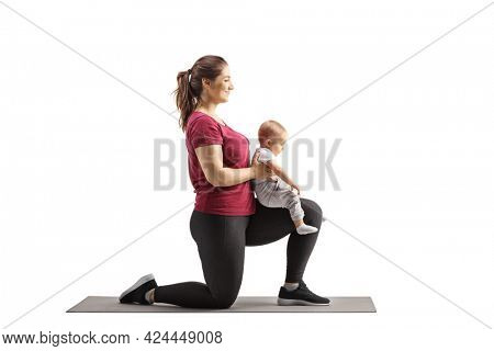 Young mother kneeling and exercisingwith her baby girl isolated on white background