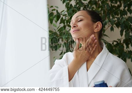 Hydrating And Moisturizing. Young African American Woman In White Bathrobe Caring Of Her Skin, Apply