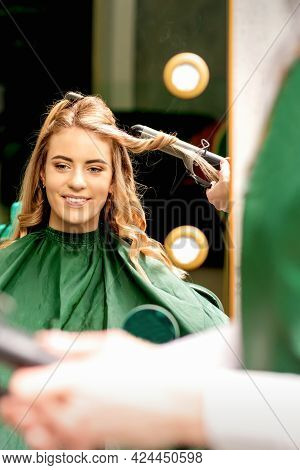 Hairdresser Using Curling Tongs Curls Long Brown Hair On The Young Caucasian Girl In A Beauty Salon