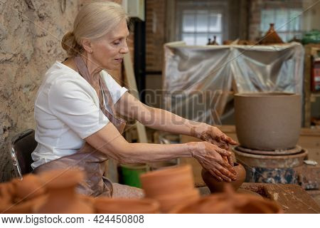Senior Female Potter Sculpts A Clay Pot. The Sculptor Works With Clay On A Potters Wheel And At A Ta