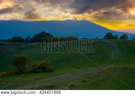 Mountainous Countryside At Dawn. Trees On Hills And Grassy Meadows. Ridge In The Distance Under The