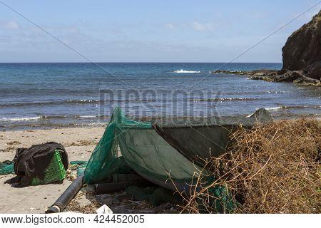 Fisherman's Net Covering Boat Stranded On Beach Sand