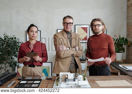 Portrait of confident multi-ethnic architects in smart casual outfits standing at table with samples and maquette while working on new design