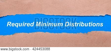 A Strip Of Blue Paper With The Inscription Required Minimum Distributions Between The Brown Paper. V