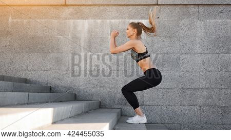 Urban Sporty Woman Training. Female Athlete Doing Squat Jumps On Urban Stairs. Fitness Motivation He