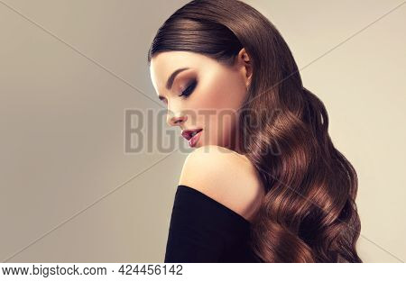Beautiful Brunette Model  Girl  With Long Curly  Hair . Woman  Wavy  Hairstyle   .  Fashion , Beauty