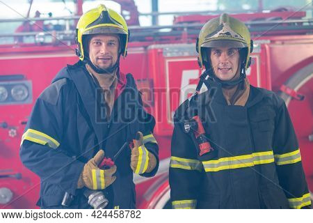 Two Fireman Or Firefighters With Safety Uniform Stand Together In Front Of Firetruck And Look At Cam