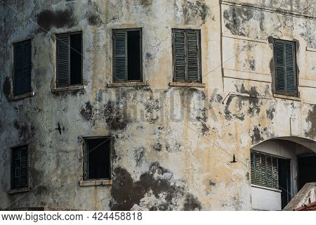 Part Of A Building In Africa Ghana And Shadow On The Wall From Two Passing Birds. Cape Coast Castle