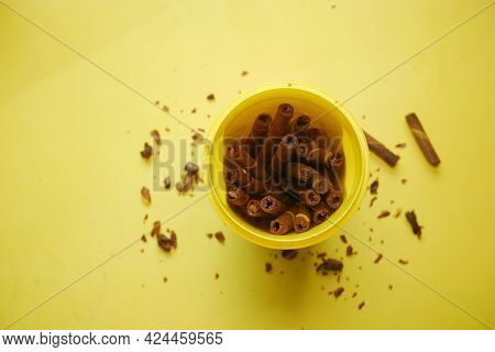 Mango Flavor Wafer Roll Chocolate In Plastic Container On Yellow Background