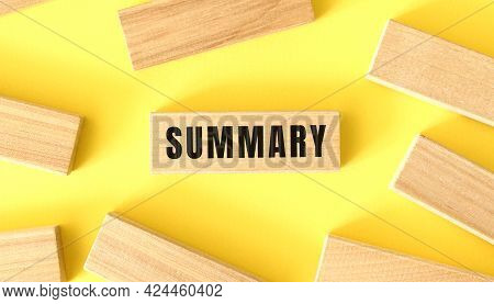 The Word Summary Is Written On A Wooden Blocks On A Yellow Background. Business Concept