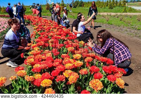 Kiev Region, Ukraine - May 10, 2021: People Taking Photos, Taking Selfie And Walking Through Flowerb