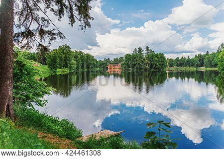 Scenic View From The Shore With Wooden Dais On Lake And Old Arch Bridge. Summer, Blue Sky, Clouds, R