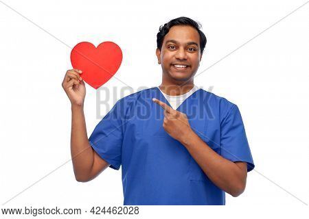 healthcare, profession and medicine concept - happy smiling indian doctor or male nurse in blue uniform with red heart over white background