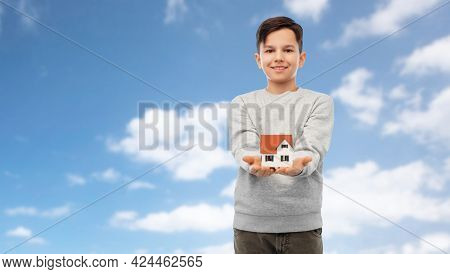 mortgage, real estate and accommodation concept - smiling boy holding house model over blue sky and clouds background